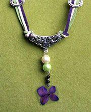 TITANIA: Juego de pulsera y collar en cuero gamuza verde, violeta y crema, con dije de flor inmortalizada y adornos plateados y de colores.