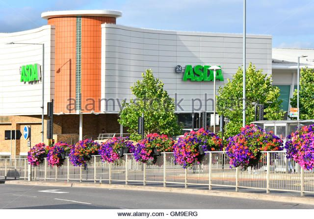 Twenty four hour Asda Supermarket shopping centre in Rugby town centre with summer flower displays along dual carriageway Warwickshire England UK - Stock Image