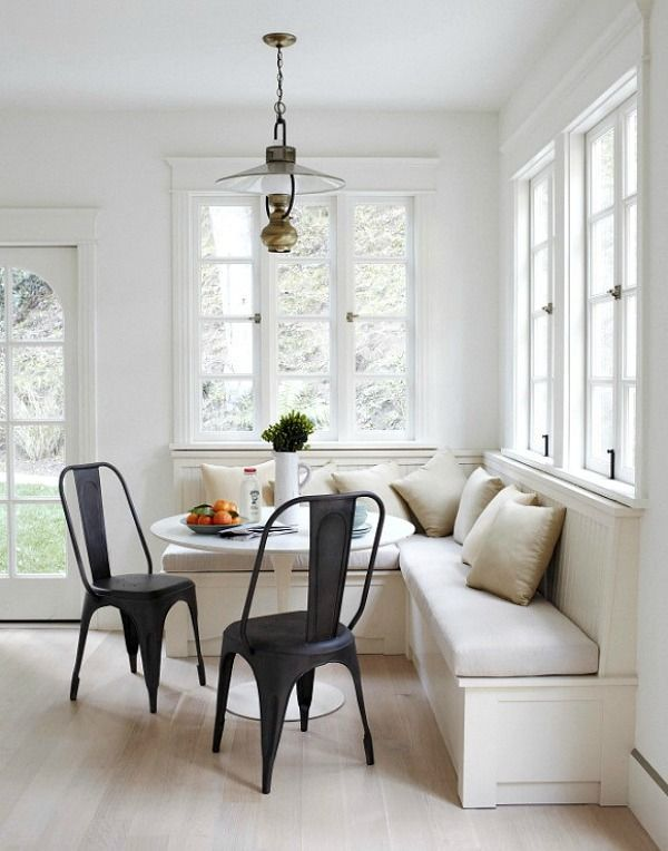 Industrial chic eat-in breakfast nook. 2 black industrial metal chairs and built-in bench seating. This eat-in kitchen has a light and airy feel with walls of windows