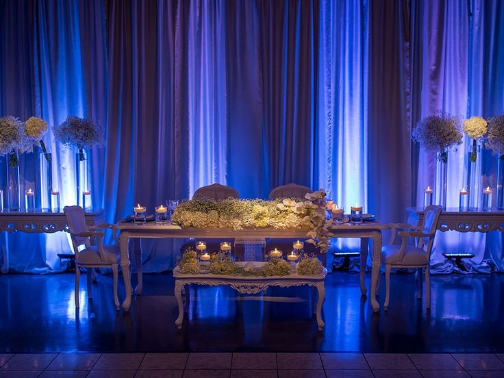 Romantic head table decorated with bunches of baby's breath, hydrangea and orchids.