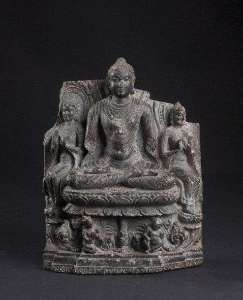 Stèle bouddhique inscrite. Bengladesh , X-XIème siècle. Le Bouddha est représenté au centre, assis dans la position de la méditation sur un trône aux lotus. Sa base est sculptée d'adorants et feuillages et inscrite en frise Le Bouddha et les deux figures analogues, assises à l'européenne de part et d'autre, effectuent tout le geste de la mise en branle de la roue de la loi. Ils sont tous trois vêtus d'une robe monastique très fine au plissé arrondi. Dans leur dos, des mandorles à bordure…