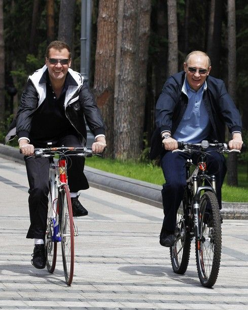 Vladimir Putin (President of Russia) and Dmitry Medvedev (Prime minister of Russia) riding bikes.