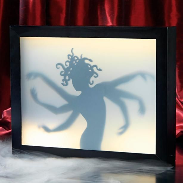Armed and dangerous delightfully grotesque Six Arm Lady    Shadow Box woos you with her hypnotic dance. A simple switch, and the box    illuminates from behind this Medusa-like figure, her six arms gliding up    and down attempt to entrance you into full Halloween gala mood.    Box sits securely flat, or can be hung by two attached sawtooth hangers at    the back. So trip the light fantastic, you'll only find this strange    and wonderful curio here as part of the Grandin Road Hallowe...