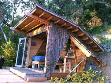 This off-the-grid hideout's folding glass front doors and hinged side walls open completely, exposing the house to cool breezes and the ocean view. It has a living roof seeded with native flowers and grasses. Salvaged redwood bark covers the structure's walls.