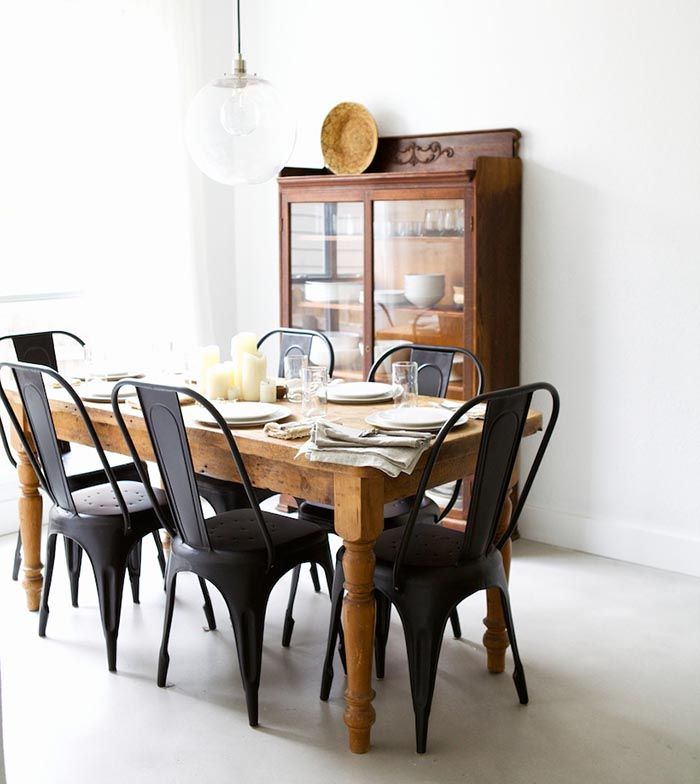 Matte black chairs with a rustic, wooden table from Pineapple Life (via Design*Sponge).