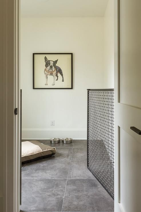 Indoor dog room with a black metal gate features large light gray concrete tiles. #DogRoom