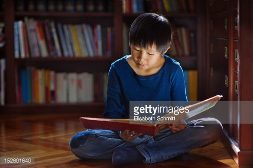 Boy sitting on floor in front of bookshelf and reading book