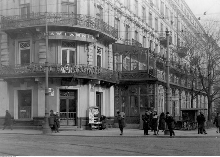 """Kawiarnia """"Gastronomia"""" przy zbiegu ulic Nowego Światu i Alej Jerozolimskich-widok zewnętrzny. Widoczny kiosk z gazetami."""