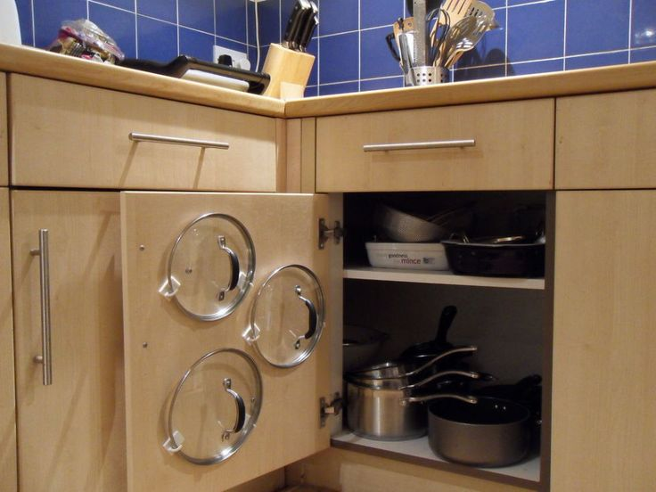 13 Sneaky Smart Ways to Use Adhesive Hooks and Strips: The awkward shape of these kitchen staples makes them difficult to store. Fashion a handy holder with two hooks that keeps lids up and out of the way. #organization #storage