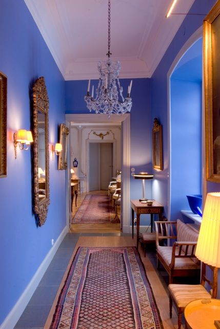 The blue wall colour picks up on the client's glass collection, and becomes a pungent backdrop for the gold details. It is a way of making the corridor more than just a walkthrough room: it can be a space for displaying your favourite pieces. #Bench #BlueInterior #BlueWalls #Chandelier #Corridor #CrystalChandelier #GoldFrame #GoldFrameMirror  #GreyDoors #GreyDoubleDoors #Hallway #KleinBlue #PersianRug #PictureLight #WoodAndStoneFloor #YellowShade