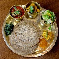 タカリ・コーゲンセット(Thakali Khogen set) 大森西口徒歩1分!東京ではここでしか食べられない、ネパールの少数民族「タカリ族」の料理が味わえるお店です☆ ヒマラヤの高地に生息するハーブや香辛料をふんだんに使っています。 ネパールにはさまざまな民族の人がいて、それぞれ違った特徴のある民族料理があります。 その中でもタカリ族はおいしい食事を作るので有名で、ネパールでも高級料理として人気を集めています。「タカリバンチャ」とは、「タカリ食堂」という意味。他店では食べられない珍しい料理の数々は女性にも大人気です^^ 本場ネパールの味を日本人にも味わいやすく仕上げています。 また、そば粉を使ったヘルシーなタカリコーゲン(そば粉クレープ)や、もちもちした食感のナンも人気♪