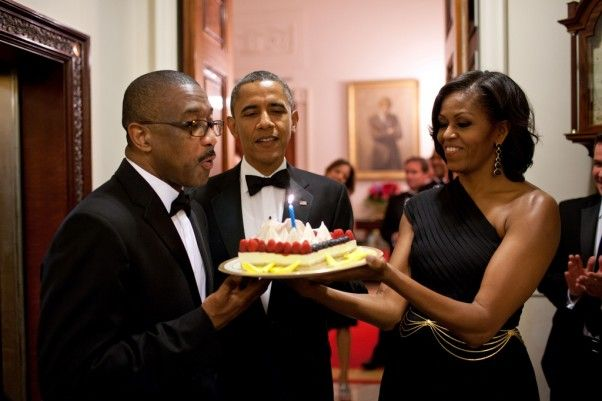 President Barack Obama and First Lady Michelle Obama present a birthday cake to...