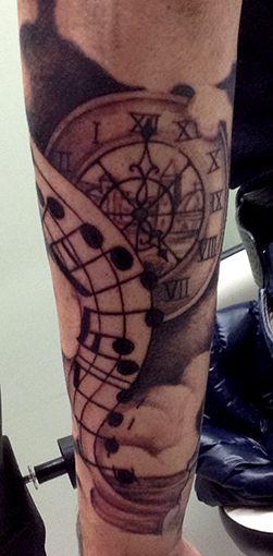 Tatuaggio braccio, orologio con paesaggio e note musicali. #tattooarm #tattooblackandgray #clockandmusic