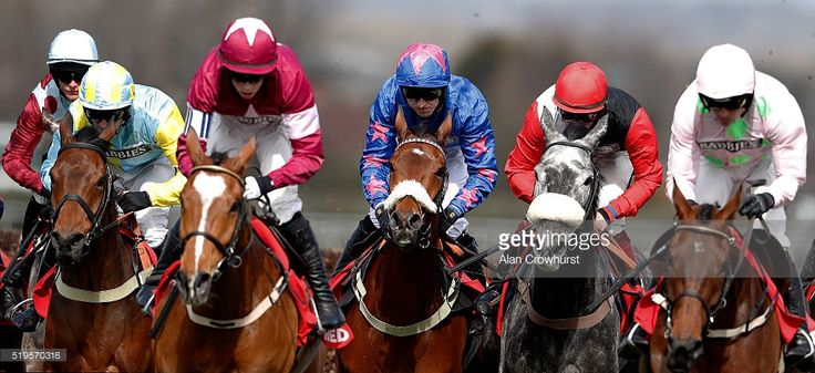 Paddy Brennan riding Cue Card (C, blue) on their way to winning The Betfred Bowl Steeple Chase at Aintree Racecourse on April 7, 2016 in Liverpool, England.