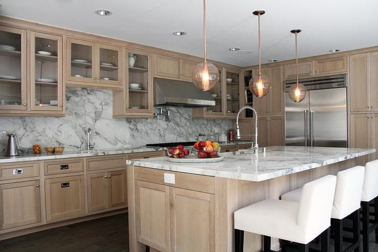 Beautiful kitchen features wire brushed oak cabinets paired with grey and white marble countertops and backsplash.