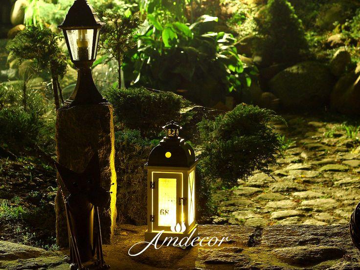 Biały lampion z czarnym daszkiem na ogrodzie nocą.  White lantern with a black cap on the garden at night.
