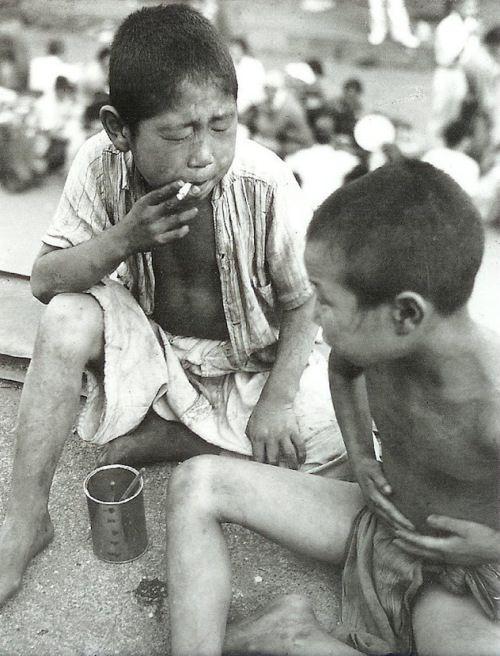 Street orphans by Hayashi Tadahiko / 林 忠彦 (1918-1990) 1946, at Ueno. 煙草をくゆらす浮浪時児(上野・昭和21年)