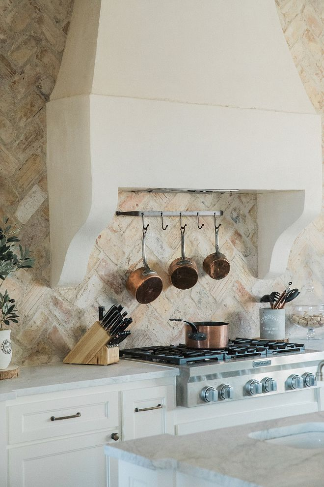 French Kitchen Most beautiful French kitchen with custom stucco hood in a soft creamy white and reclaimed brick backsplash set in a herringbone pattern