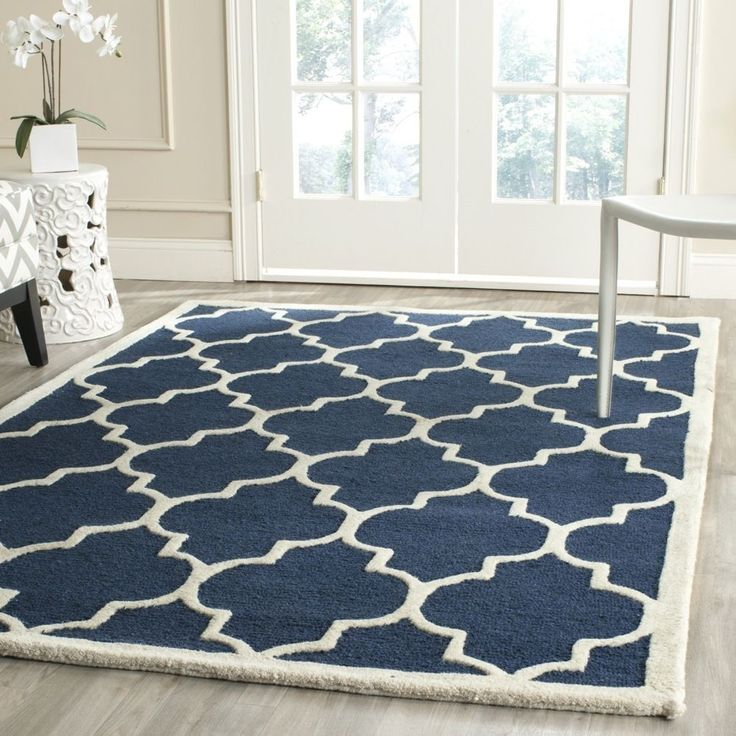 Intricately designed with an abstract pattern laid out in rich colors of navy and ivory, this gorgeous Moroccan wool rug is ideal for contemporary and transitional decors. Hand-tufted using the finest wool pile, this piece is exquisite.