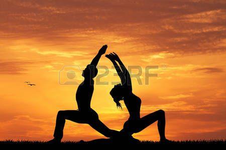 yoga couple: coppia facendo yoga silhouette al tramonto Archivio Fotografico
