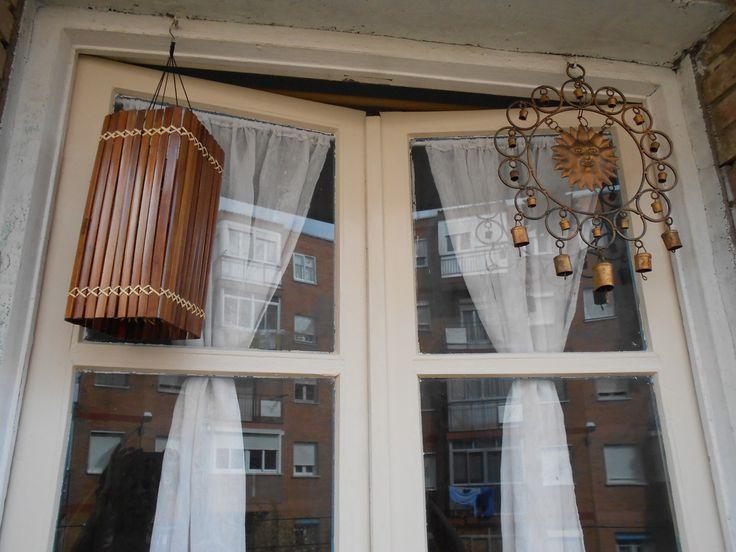 puerta de balcón entreabierta, con colgantes de viento.