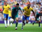 Oribe Peralta of Mexico and Juan Jesus of Brazil chase down the ball