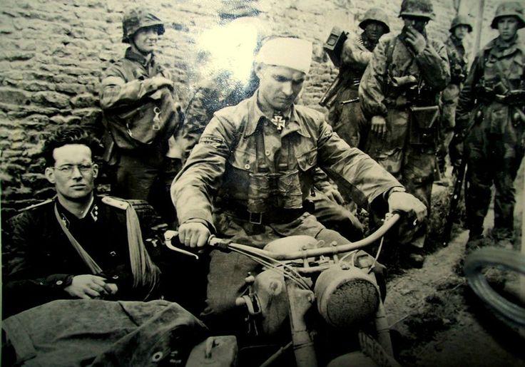 Dans le secteur de Rots le 9 juin, Max Wünsche blessé à la tête est venu rendre visite à un groupe de grenadiers de la 12e SS-PzDiv Hitlerjugend. L'officier dans le side car s'appelle Rudolf von Ribentropp qui n'est autre que le propre fils du ministre des affaires étrangère du IIIe Reich Joachim von Ribentropp condamné à mort à l'issue du procès de Nuremberg et éxécuté  en 1946. (Bundesarchiv).