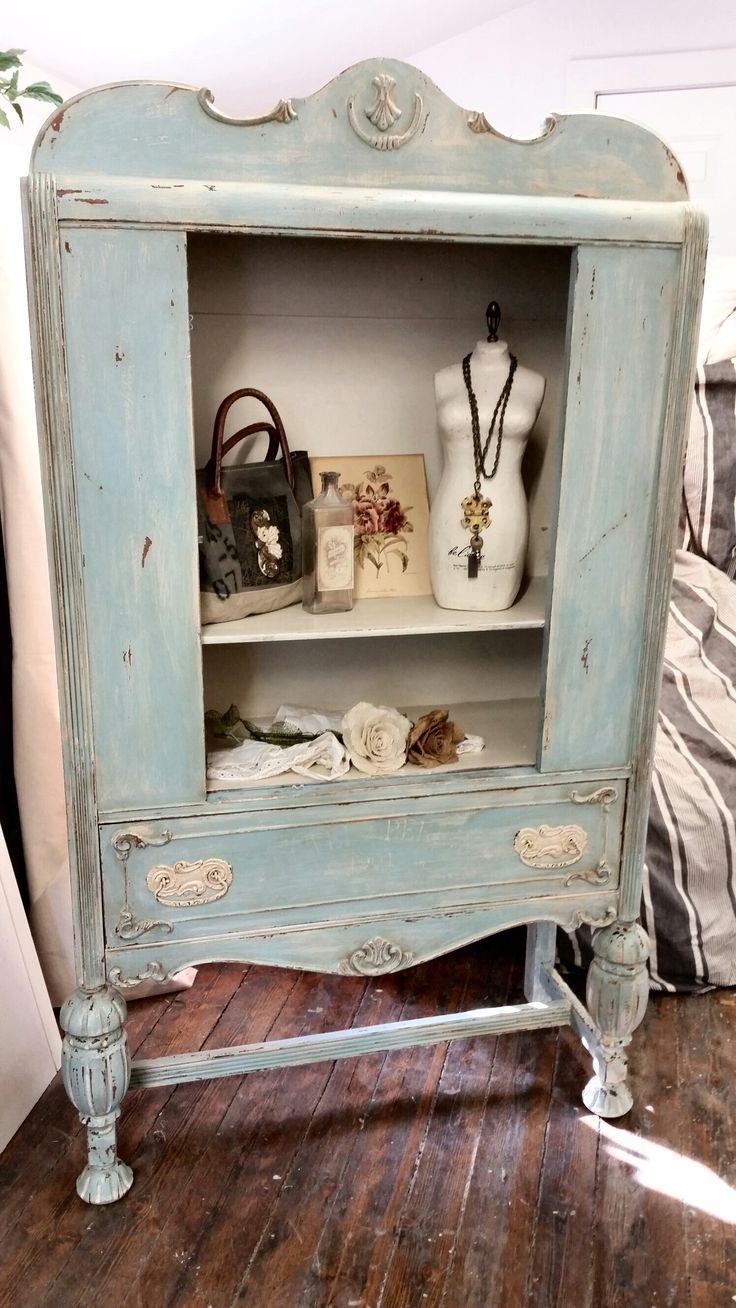 weathered romantic shabby antique cabinet painted in chippy layers of whites, blues & grays then distressed. see more of our work on facebook