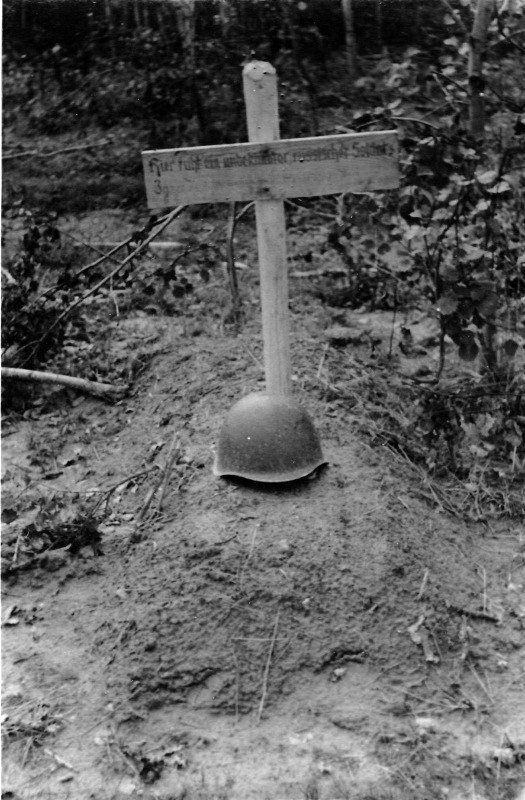 """Могила неизвестного советского солдата похороненного немцами. 1941 год. Надпись по-немецки: """"Здесь лежит неизвестный русский солдат."""""""