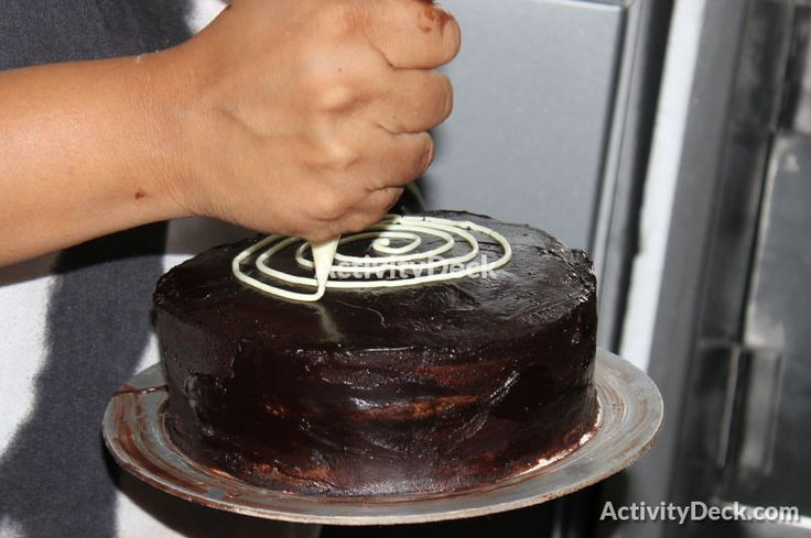 The instructor demonstrates a decoration method(Feathers) for a triple chocolate cake