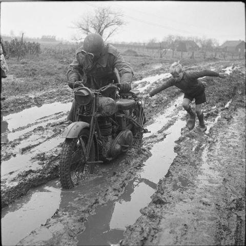 Children in Wartime-Dutch boy helps a British motorcycle dispatch rider negotiate a muddy road in Holland, Dec1944.