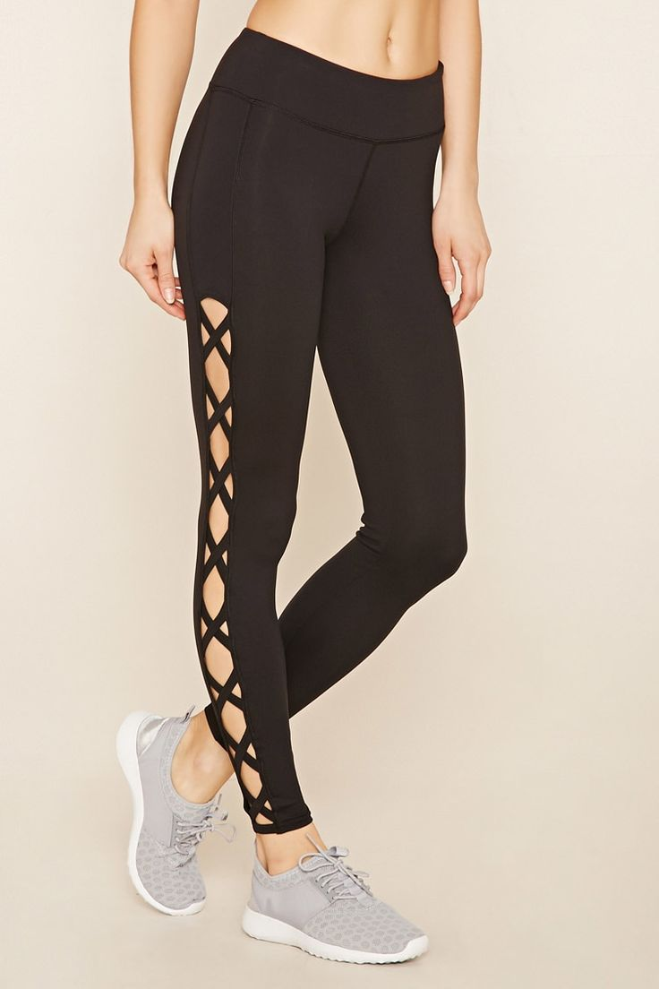 A pair of stretch knit athletic leggings with crisscross-cutout sides, a hidden key pocket, and moisture management.