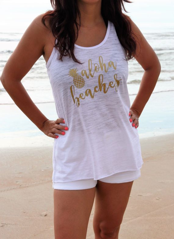 "Say hello to the the beach with a white slub women's flowy racer back tank with a gold ""aloha beaches and pineapple"" print. Perfect to wear over your swimsuit! Printed on 91% poly 9% combed and ring-s"