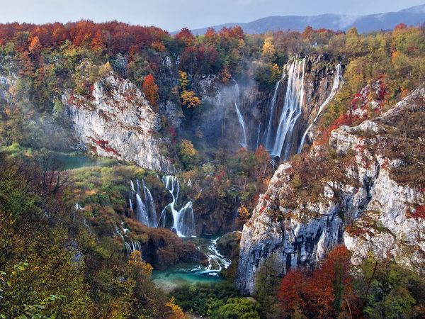National Geographic.  Falls in Autumn Dispersing fog and a moment of sunshine bring the falls and foliage of Croatia's Plitvice Lakes National Park into view on an early autumn morning. The country's oldest and largest national park, Plitvice boasts more than plunging waterfalls: Its 16 terraced lakes, formed by natural travertine dams, change color throughout the day, and its abundant wildlife includes 261 species of birds.