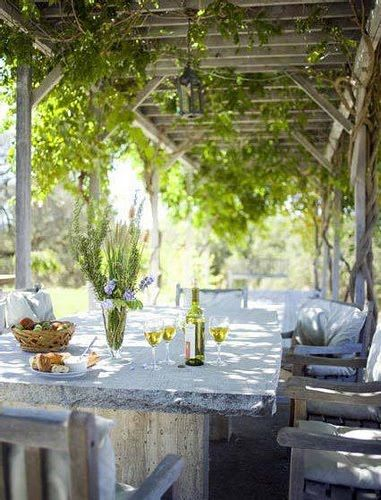 Rustic and organic natural stone table for alfresco dining under the pergola with vines - lovely!