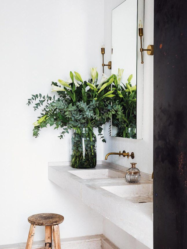 plants in bathroom | white bathroom | vanity | concrete | brass sconce