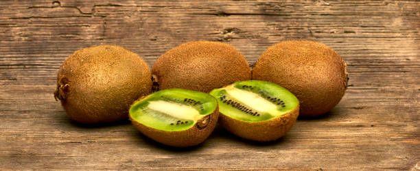 fresh group of kiwi fruits full and sliced on wood table background