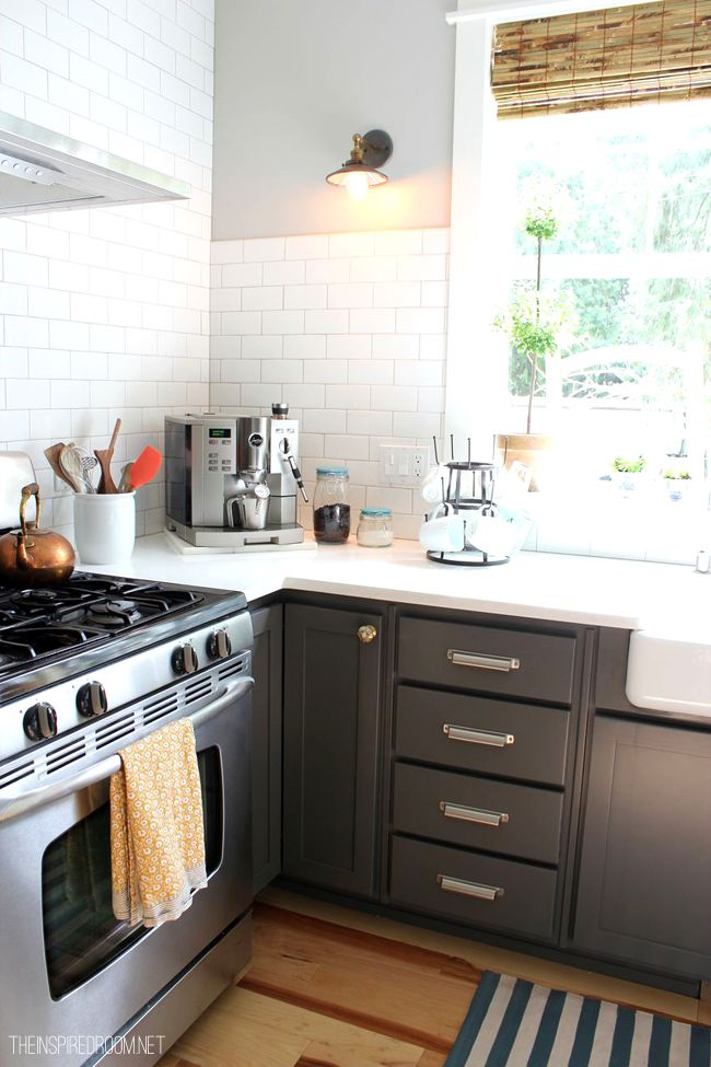 gray kitchen cabinets and white counter with coffee station and mug rack