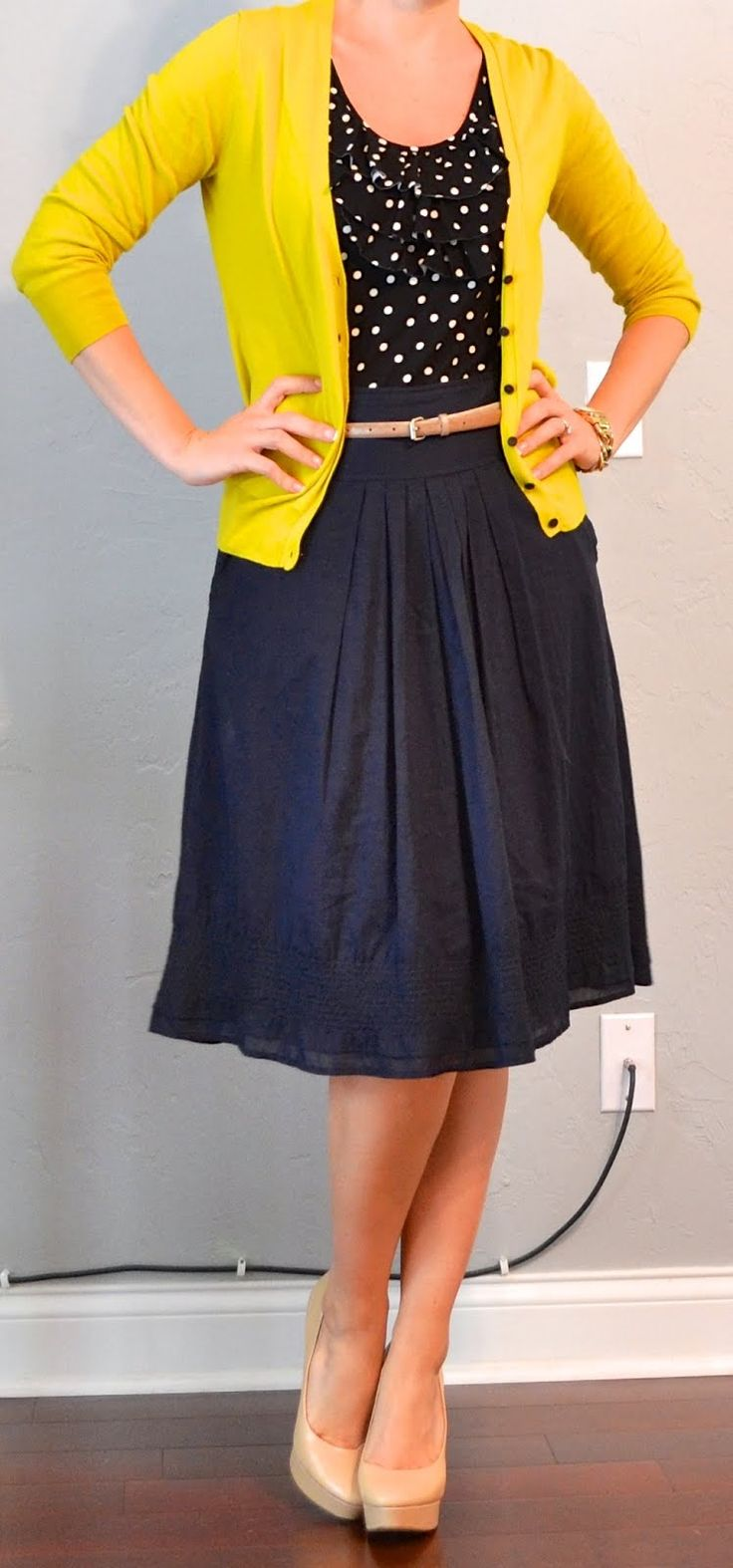 yellow cardigan, black polka dot blouse, navy skirt, nude shoes, nude belt