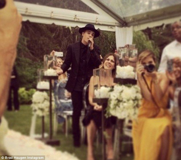 The wedding singer! Justin Bieber breaks into song as his manager Scooter Braun ties the k...