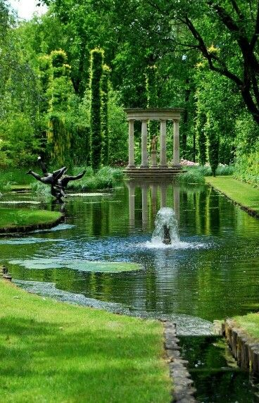 Serene garden with a small pond, fountain, sculpture, and columns, and more, just lovely.