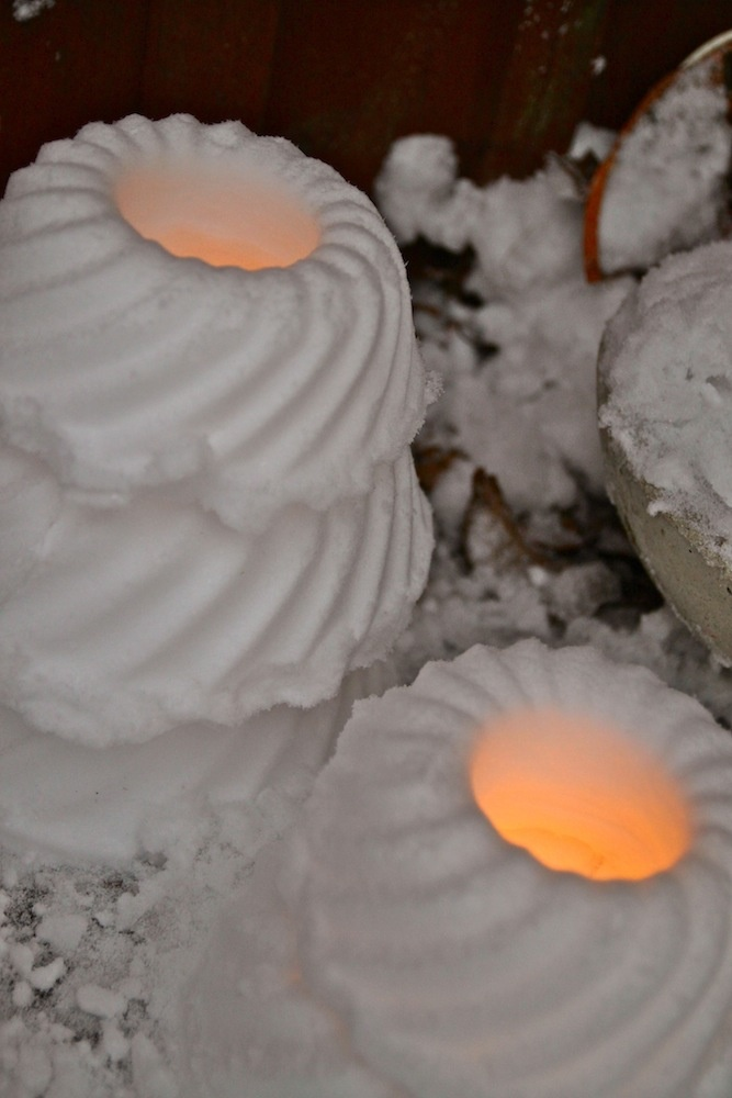 Winter onederland. Pack snow into cake molds, then tap to slide out. Place tea candles in the middle. Gives off a welcoming, warm glow during the holidays when placed along the walkway or front steps to your home.