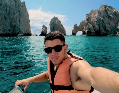 [Jealousy] Nick Jonas is on vacation in some secluded island. On a boat with his life jacket and sun glass. {Blue water/tall mountains}