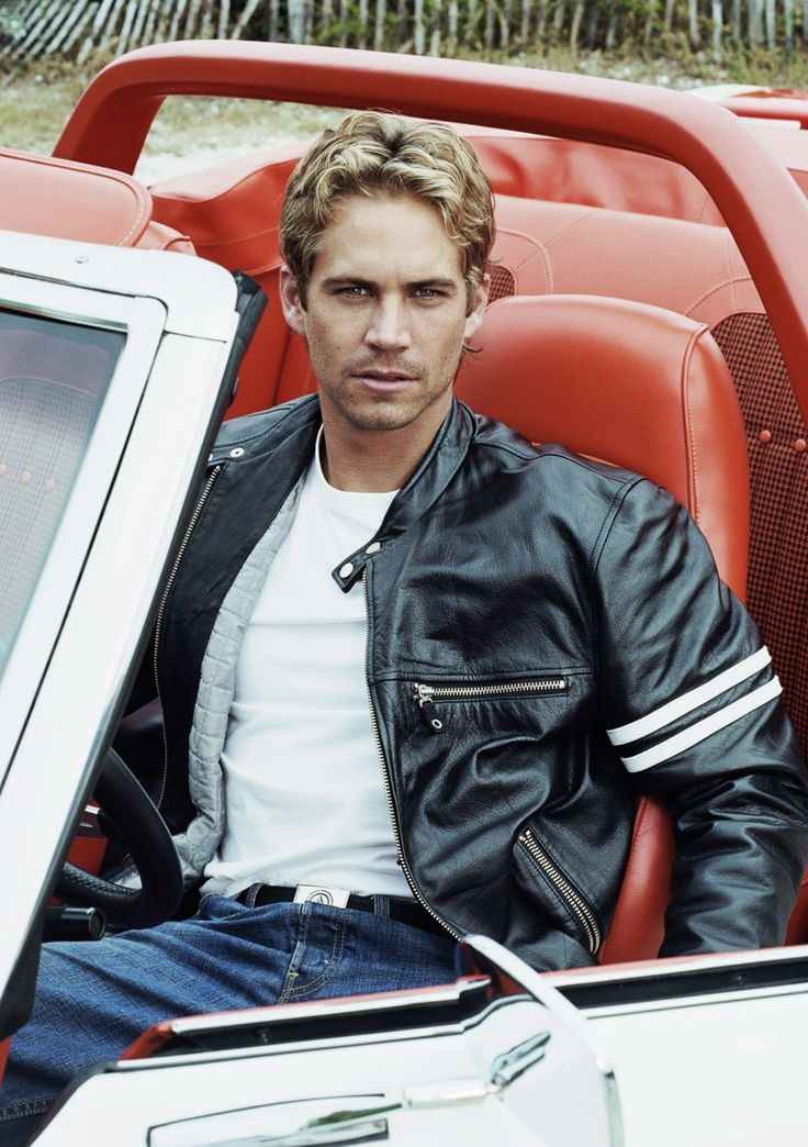 Paul Walker sitting in classic red leather car wearing black leather jacket