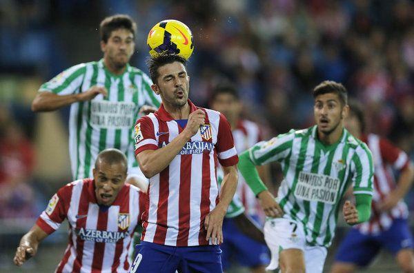 Villa salta, en el centro de la imagen, para despejar el balón rodeado de jugadores béticos