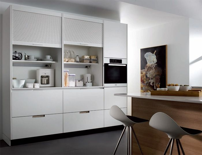 SANTOS kitchen | Minos, capacity and accessibility. A kitchen layout with tall units permits multiple functions in a reduced space: a storage and preparation area inside the rolling shutter units, a fridge with pull-out drawers and an oven.