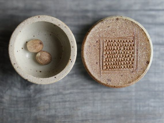 ceramic lidded jar with grater surface on the lid; grating surface for nutmeg, garlic and ginger. this ceramic jar is a multifunctional accessory in