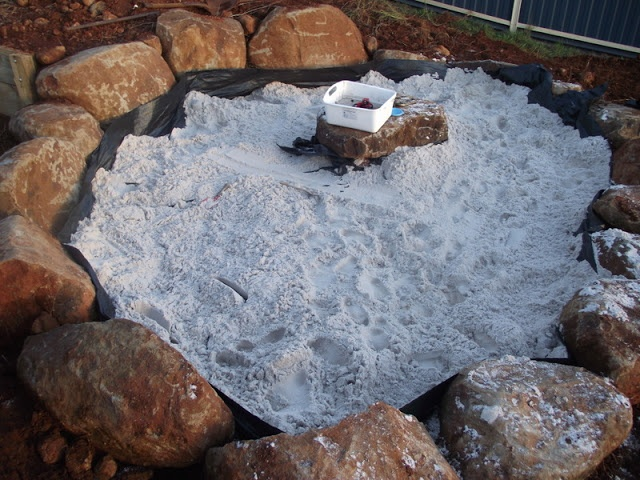 Using natural resources to build a sandpit and invite play...