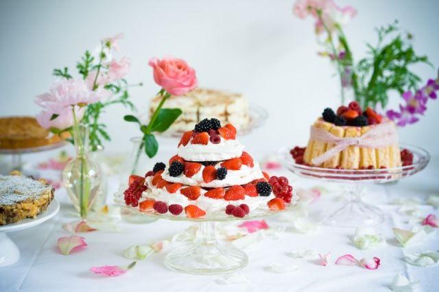 Taartentafel met rood fruit taarten op plateaus en bloemdecoratie met bloemblaadjes