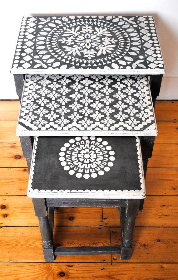 An upcycled vintage wooden table nest. The tables are painted and stencilled using the finest quality Annie Sloan chalk paint.  Each table has a different stencil design on the top. All stencils are original designs, hand cut in my studio.    Any imperfections should be seen as part of the charm of this one-off original piece.    These tables are unique and would make a lovely original addition to your home.    Colour: Graphite and Old White   Dimensions:Largest Table  height 47cms  width…